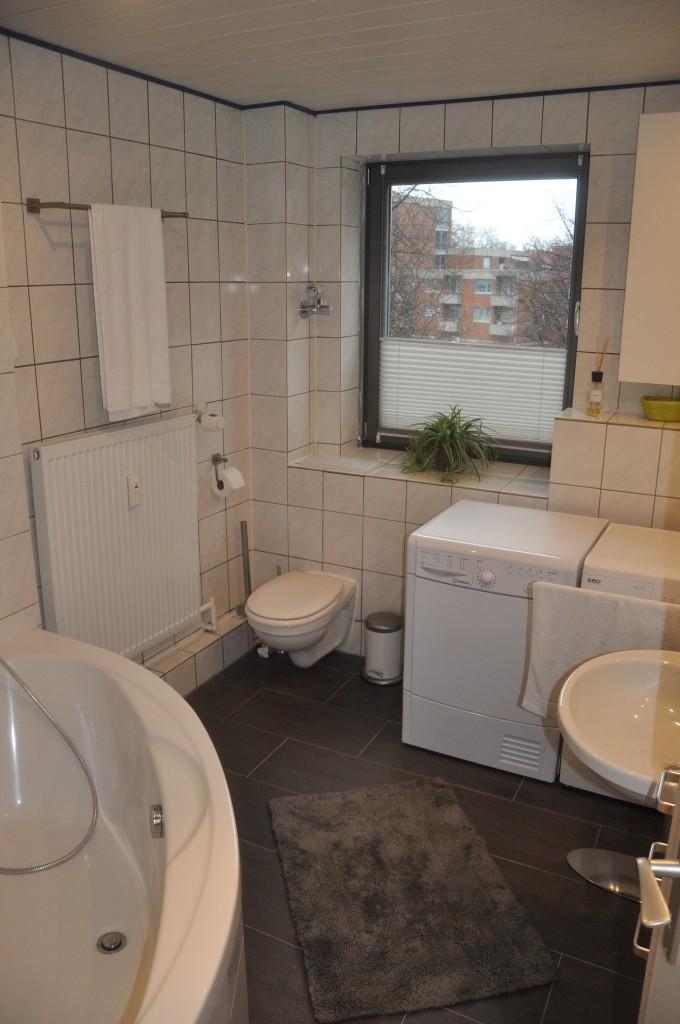 Geräumiges Badezimmer mit Eckbadewanne, Waschmaschine und Wärmepumpentrockner